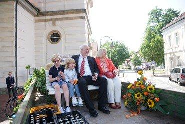 Pastor Korn sitzt auf dem Anhänger, auf dem er mit dem Trecker nach Hause gebracht wird.