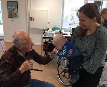 Baby, mor og smilende ældre mand på et plejehjem