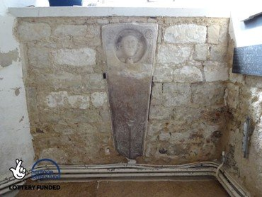 Plaster removed round inset stone coffin lid