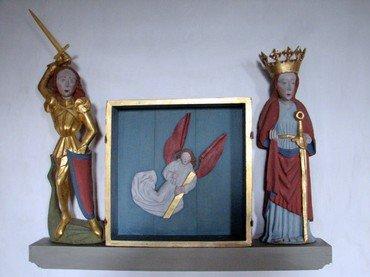 Til venstre Skt. Jørgen med løftet hånd, hvori sværdet mangler. Det vil sige: Pludselig en dag opdagede vi at en lokal borger har snedkereret et nyt sværd til Sankt Jørgen.