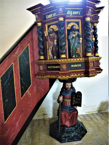 Moses med lovens tavler bærer prædikestolen med Kristus og de fire evangelister – det gamle testamente er grundlaget for det nye.