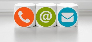 Tre terninger med hver deres logo. En med en telefon, en med et @ og en med et brev
