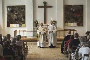 Kirkens præster foran alter ved gudstjeneste