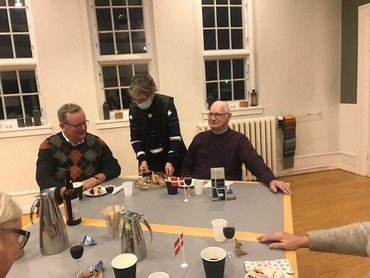 Et billede, der indeholder fire personer ved et bord. Der er kaffe, gaver og flag på bordet.