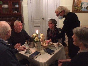 Et billede af fire personer siddende omkring et bord. Der er opdækning til kaffe og salmebøger på bordet.