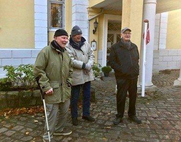 Et billede af tre personer, der står udenfor en gul bygning med hvide søjler ved indgangspartiet.
