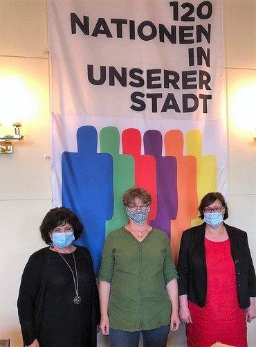 Drei Frauen stehen vor einer Fahne