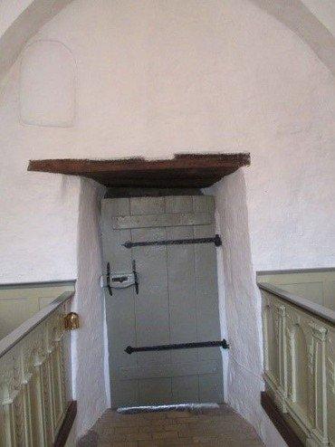 Et lille tilmuret romansk vindue ses over inderdøren.