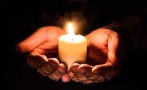 To hænder bærer et levende lys
