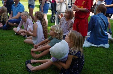 Børn sidder og ser på tryllekunstner