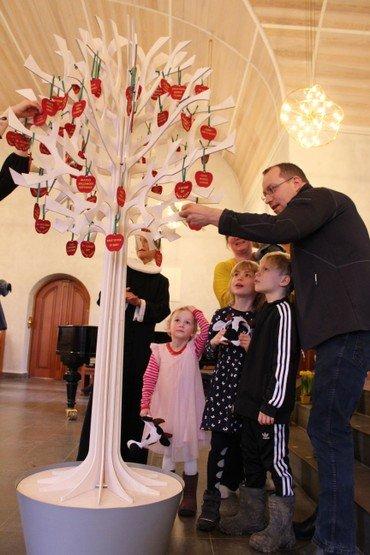 Familie står omkring kirkens dåbstræ og tager deres æble ned.