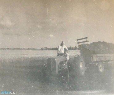 """1950-70: Traktoren (med barn på førersædet) forspændt """"gummivognen""""."""