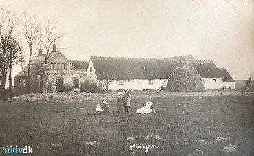 """1917 – Det ældste billede af gården, set fra nord. Det grundmurede stuehus er bygget af den tidligere ejer (Jens Peter Larsen 1890-1906). Foran nordlængen er det korn, som der ikke var plads til i laden, sat """"i hæs"""".  – Forrest i billedet Karen Andersen med Ernst (f. 2.10. 1916) på skødet, dernæst Dagny (f. 1913) og den ældste, Rigmor (1909). Til højre tjenestepigen (navn ukendt)."""