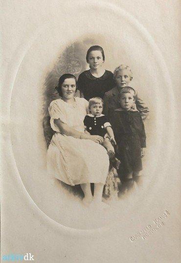 1923 – Rigmor i konfirmationskjole med lille Thormod (f. 29.4. 1923) på skødet. Stående Dagny (f. 1913), Ernst (f. 2.10. 1916), Henning (f. 1.11. 1919).