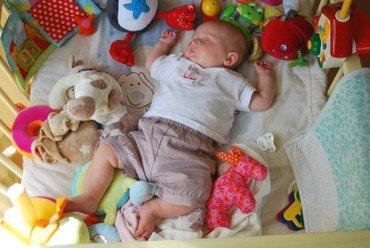 Baby sover blandt legetøj