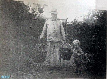 Emil Frederiksen med barnebarnet Poul Emil på frugtplantagen ca, 1950. Frugten blev samlet ind i store kurve. Bemærk åget, som lagde vægten op over skuldrene.