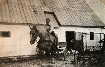 Mogens højt til hest. Bemærk hesteriven til højre – og prøv at tælle kattene, som styrter ud af stalddøren.