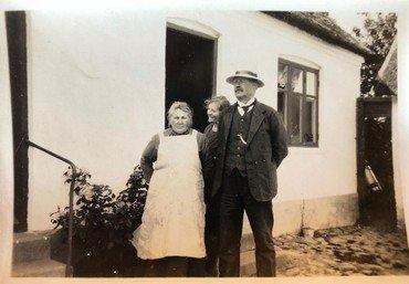Kirstine og Henrik på gårdspladsen sammen med datteren Olga. Kirstine døde 28.2. 1929.