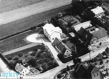 """Møllehuset og motormøllen 1950. Til venstre """"Møllevang"""", til højre Brugsen."""