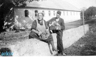 Foto fra Lysegård. Siddende foran svinehuset Holger Andersen med hund. Kvinden er ukendt.  Cirka år 1930.