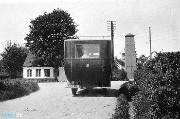Bussen fra Tune ved udkørslen til Ved Kirken i 1920erne. Centralen med sit store træ ses til venstre, til højre transformatorstationen.