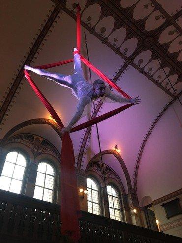 Cirkusartist hænger ned fra loftet i rødt reb.