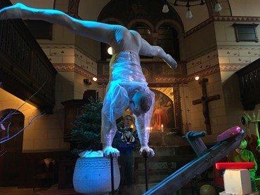Cirkusartist i gennemsigtig plastikdragt står på hænder i kirken.