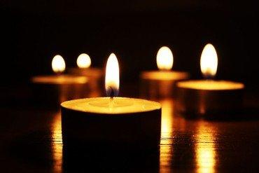 Fem fyrfadlys på bord med mørk baggrund. Flammen spejler sig i det blanke bord