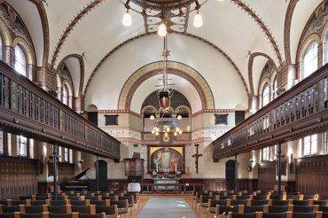 Kirkerummet set fra indgangen. Pulpiturer i begge sider over stolene. Alter og altertavle i baggrunden. Lysekronen er tændt.