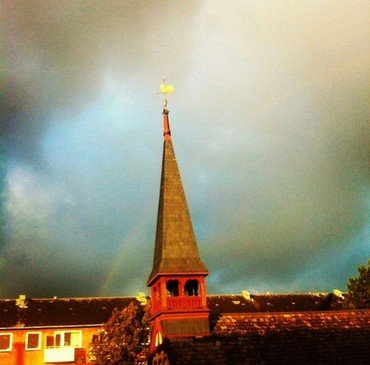 Kirketårnet belyst af solen på baggrund af blå himmel med sorte skyer og regnbue.