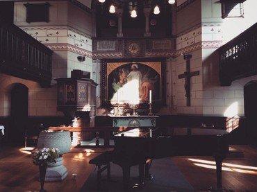 Kirkerummet, i forgrunden til venstre døbefonden og til højre det sorte flygel. Solen kaster lys på altertavlen af Kristus