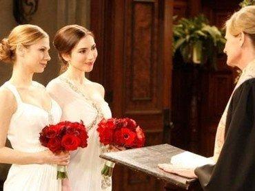 Lesbisk brudepar i hvide ens hvide brudekjoler og brudebuket af røde blomster