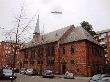 Sct. Lukas kirke fra siden ud mod Chr. Richardts Vej. Parkerede biler lang kirken. Træ og himmel i efterårsdragt