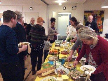 Billede af flere mennesker, der går rundt om buffeten og tager mad. De taler sammen.