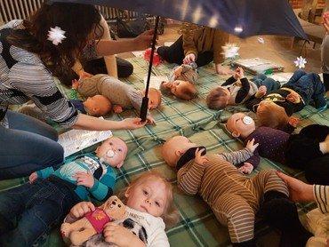 På billedet ses en rundkreds med babyer liggende på kirkens gulv