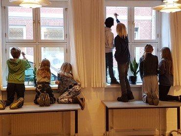 Billede af børn der tegner på vinduerne i sognehuset