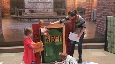 Billede af Kirsten med den store lege bibel og et barn