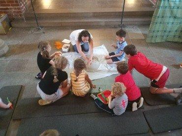 Billede af Kirsten der fortæller fadervor med sand omringet af børn