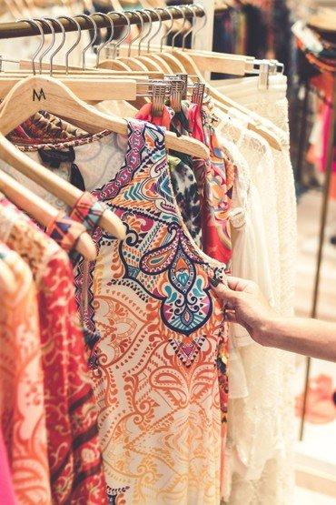 tøj der hænger på bøjler i en butik