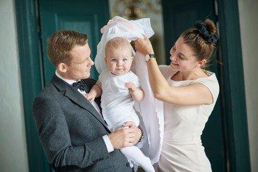 Dåbsbillede af far og mor med barn i midten