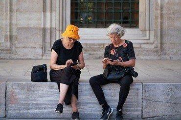 2 ældre damer som sidder med deres mobiltelefoner og skrive sms