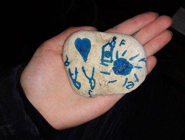 En hånd med en sten med tegning på