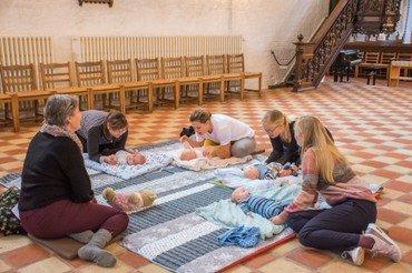 Billede af babyer og mødre på gulvet i kirken